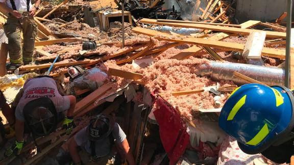 Dozens of firefighters searched for victims on the debris after the explosion.