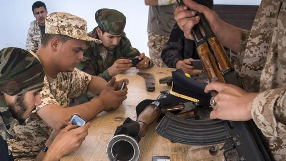 Government of National Accord forces play an online video game on their phones during a break from fighting, in a military base in Tajoura, on May 1.
