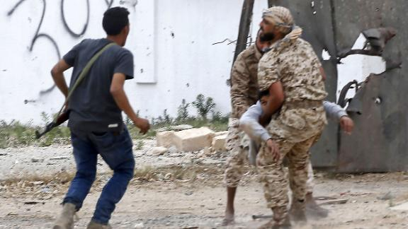 Government of National Accord fighters carry a wounded comrade during a battle on May 21 in the Salah al-Din area, south of Tripoli.
