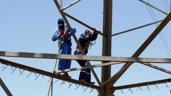 Workers operate on high voltage towers on May 23, after they were damaged by fighting.