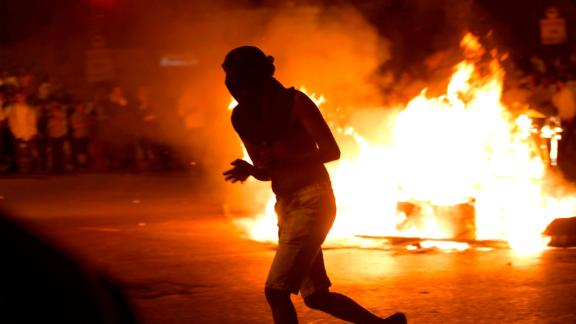A protester runs past a burning barrier at the main entrance to Jerusalem on Tuesday.
