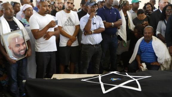 The father of Solomon Teka mourns over his body during his funeral in Haifa on Tuesday.