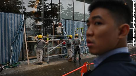 Workers repair windows that were damaged in the Legislative Council building in Hong Kong on July 3, 2019, during a protest.