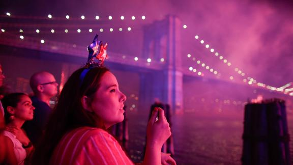 People watch fireworks light up the Brooklyn Bridge during the annual Macy's fireworks show on the East River from Manhattan July 4, 2019.