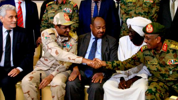 African Union envoy to Sudan Mohamed al-Hacen Lebatt, second from left, shakes hands with an army general following a press conference announcing an agreement was reached. Under the terms, the military council will be in charge of the country's leadership for the first 21 months. A civilian administration will rule the council during the following 18 months.