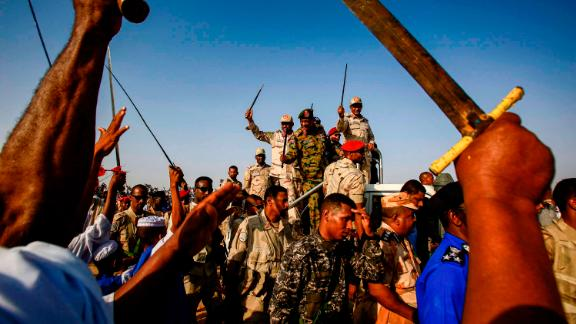 Mohamed Hamdan Dagalo, deputy head of Sudan's ruling Transitional Military Council (TMC) and commander of the Rapid Support Forces (RSF) paramilitaries, center right, waves a baton as he rides through supporters in Qarri, north of Khartoum, on June 15.