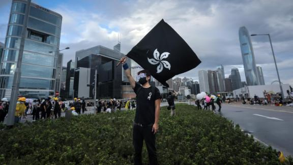 "A protester waves a ""Black Bauhinia"" flag as others set up barricades at Lung Wo road outside the Legislative Council in Hong Kong before the flag raising ceremony to mark the 22nd anniversary of handover to China early on July 1, 2019."
