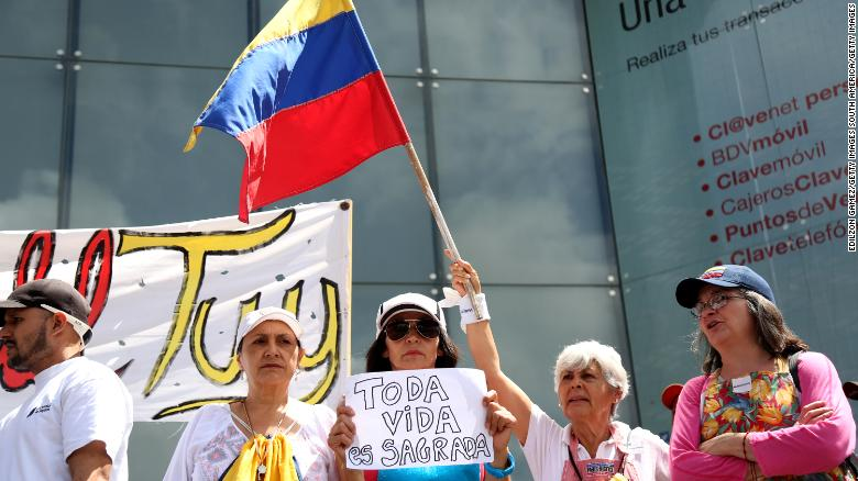 "Venezuelans wave flags and hold signs at a demonstration called by opposition leader Juan Guaidó. The motto of the protest is ""No more torture."""