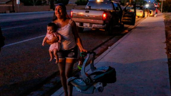 Dawn Inscore runs out of her apartment with her child after a 7.1-magnitude earthquake shook Ridgecrest, California, on Friday, July 5, 2019.