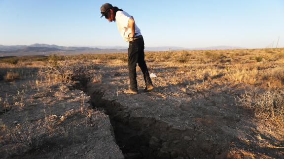 A man inspects a crack in the earth after a 6.4-magnitude earthquake struck near Ridgecrest on July 4, 2019.