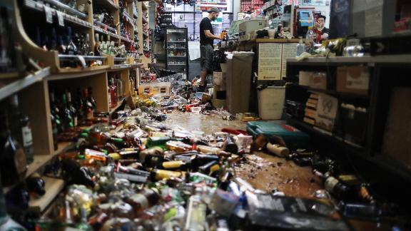 RIDGECREST, CALIFORNIA - JULY 06: An employee works at the cash register at Eastridge Market, near broken bottles scattered on the floor, following a 7.1 magnitude earthquake which struck in the area, on July 6, 2019 in Ridgecrest, California. The earthquake, which occurred July 5th, was the second large earthquake to hit the area in two days and the largest in Southern California in 20 years. The store has remained open since the 7.1 earthquake struck in an effort to serve the community. (Photo by Mario Tama/Getty Images)