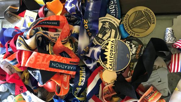 A pile of Meza's racing medals rests on a coffee table at home.
