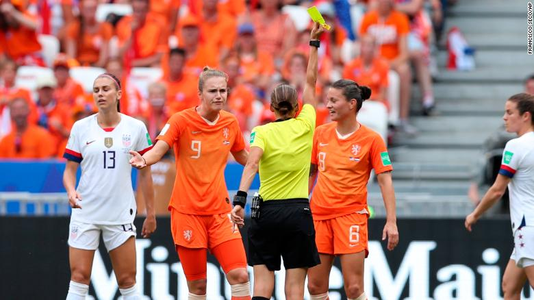 Referee Stephanie Frappart shows an early yellow card.