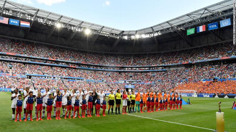 The teams stand for their national anthems before the match.