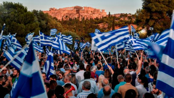 New Democracy supporters waved Greek flags at a rally for Mitsotakis in Athens.