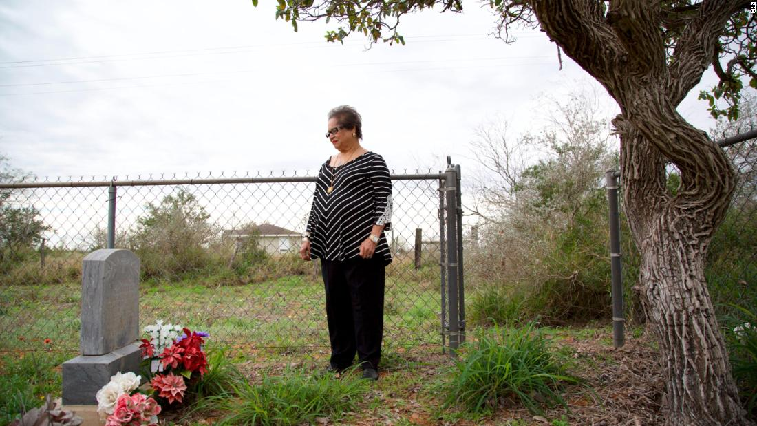 Melba Coody stands at the graves of Bazán and Longoria in Texas' Rio Grande Valley.