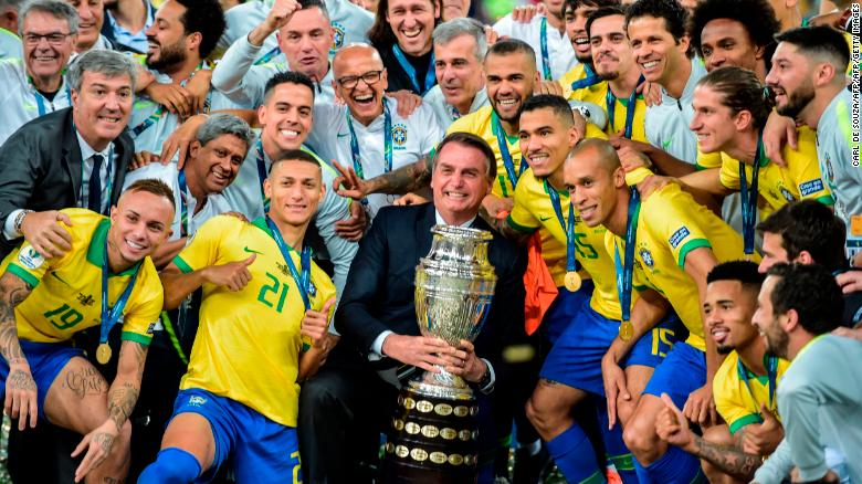 Brazilian President Jair Bolsonaro holds the Copa America trophy as members of the national team celebrate.
