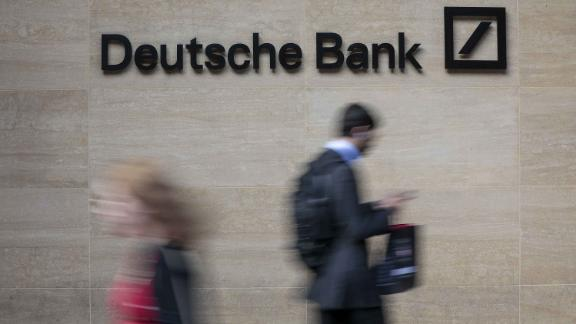 Pedestrians pass in front of a sign at offices of Deutsche Bank AG in London, U.K., on Monday, July 8, 2019. Deutsche Bank announced a sweeping turnaround plan that will transform Germany