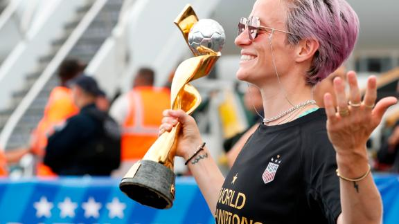 United States women's soccer team member Megan Rapinoe holds the Women's World Cup trophy as she poses for the media after arriving with the rest of the team at Newark Liberty International Airport, Monday, July 8, 2019, in Newark, N.J. (AP Photo/Kathy Willens)