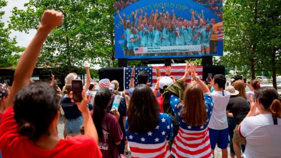 USA's players are seen on a screen celebrating, as fans watch the France 2019 Women's World Cup final football match.
