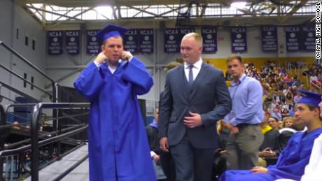 High school students offer a silent ovation while a classmate with autism receives his diploma