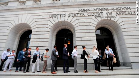 People wait in line to enter the 5th Circuit Court of Appeals to sit in overflow rooms to hear arguments in New Orleans, Tuesday, July 9, 2019. (AP Photo/Gerald Herbert)