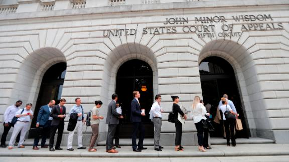 People wait in line to enter the 5th Circuit Court of Appeals to sit in overflow rooms to hear arguments in New Orleans, Tuesday, July 9, 2019. The appeals court will hear arguments today on whether Congress effectively invalidated former President Barack Obama