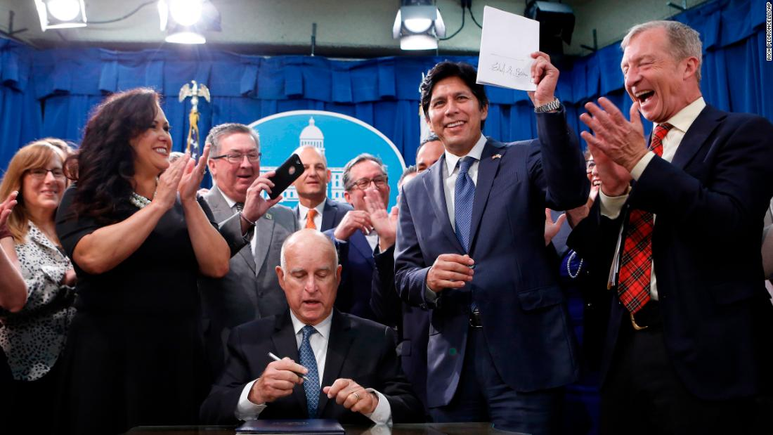 Steyer stands next to California state Sen. Kevin de Leon, who is holding a copy of State Bill 100 after it was signed into law by California Gov. Jerry Brown in September 2018. SB100 sets a goal of phasing out all fossil fuels from the state's electricity sector by 2045.