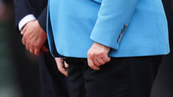 "The hands of Merkel and Finnish Prime Minister Antti Rinne are seen as they listen to national anthems in Berlin in July 2019. Merkel's body visibly shook again, raising concerns over her health. She said she was fine and that she has been ""working through some things"" since she was first seen shaking in June."
