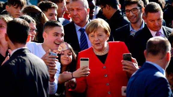 Merkel poses for photos with students as she visits a secondary school in Berlin in April 2019.