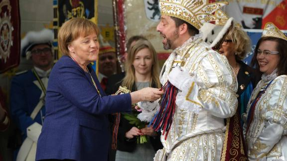 Merkel touches the scepter of a Carnival prince during the annual Carnival reception in Berlin in February 2019.