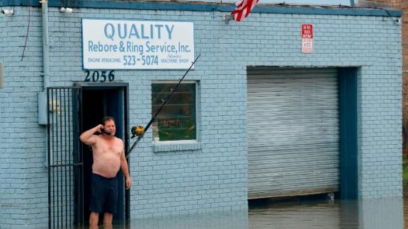 David Fox makes a call from his businest in New Orleans after flooding in New Orleans Wednesday, July 10, 2019.