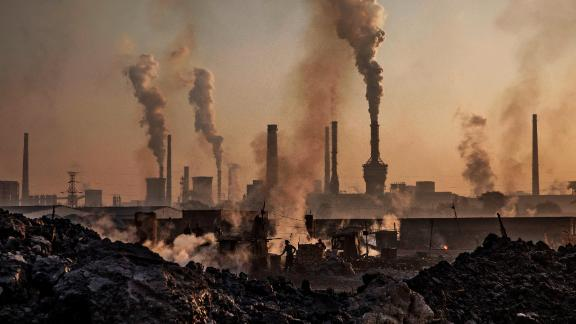 "INNER MONGOLIA, CHINA - NOVEMBER 04: Smoke billows from a large steel plant as a Chinese labourer works at an unauthorized steel factory, foreground, on November 4, 2016 in Inner Mongolia, China. To meet China's targets to slash emissions of carbon dioxide, authorities are pushing to shut down privately owned steel, coal, and other high-polluting factories scattered across rural areas. In many cases, factory owners say they pay informal 'fines' to local inspectors and then re-open. The enforcement comes as the future of U.S. support for the 2015 Paris Agreement is in question, leaving China poised as an unlikely leader in the international effort against climate change. U.S. president-elect Donald Trump has sent mixed signals about whether he will withdraw the U.S. from commitments to curb greenhouse gases that, according to scientists, are causing the earth's temperature to rise. Trump once declared that the concept of global warming was ""created"" by China in order to hurt U.S. manufacturing. China's leadership has stated that any change in U.S. climate policy will not affect its commitment to implement the climate action plan. While the world's biggest polluter, China is also a global leader in establishing renewable energy sources such as wind and solar power. (Photo by Kevin Frayer/Getty Images)"