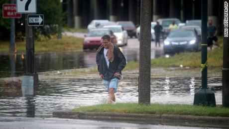 A man runs through stagnant water in New Orleans.