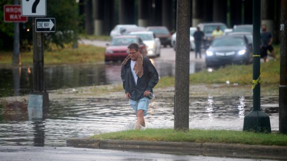 A man walks through standing water in New Orleans after a severe thunderstorm caused flooding.