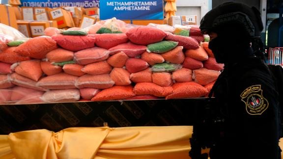 A police officer from Thailand's Narcotics Control Board stands guard in front of bags of methamphetamine pills in Ayutthaya province, north of Bangkok.
