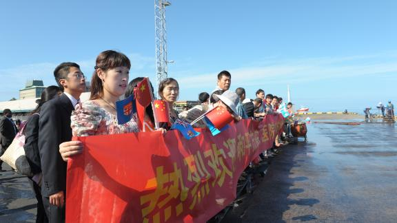 Chinese Fijians display banners on the arrival of the Peace Ark, the hospital ship of China's People's Liberation Army Navy, at Suva Port in Suva, Fiji, on August 22, 2014.