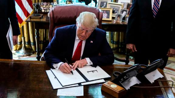 President Trump signs an executive order imposing fresh sanctions on Iran in the Oval Office on June 24.