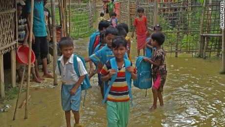 Rohingya children walking in the floodwater with their school bags going to their learning center. (July 7, 2019)