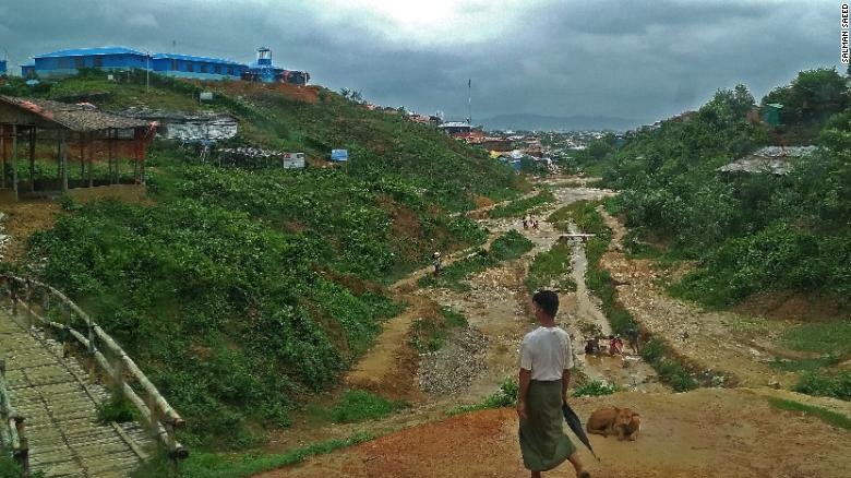 A Rohingya man walks through the refugee camp to his home before another round of rain.