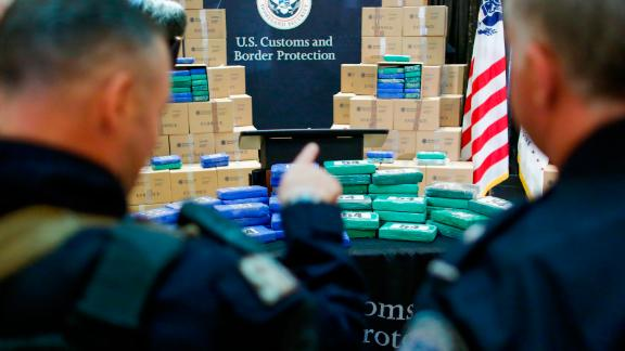 Police officers stand guard near cocaine seized from the cargo ship.