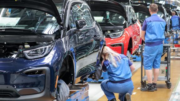 20 May 2019, Saxony, Leipzig: Employees at the BMW plant in Leipzig work on the assembly of the i3. The plug-in hybrid has been built at BMW