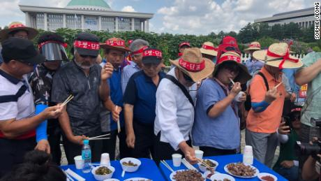 Members of the Korea Dog Farmers' Association eat dog meat in front of the National Assembly as part of their protest against putting ban on dog meat consumption.
