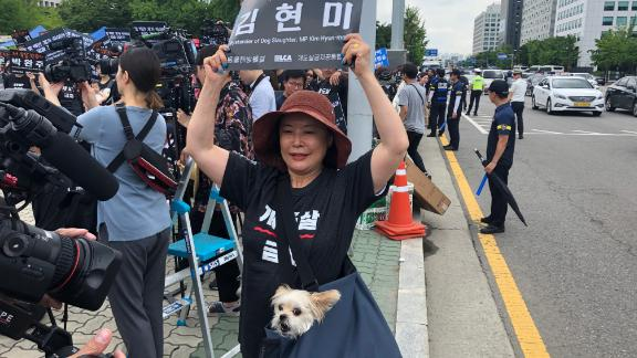 """A protester against the dog meat trade holds up a sign reading """"Bystander of Dog Slaughter, MP Kim Hyun-mee"""" outside South Korea"""