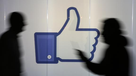People are seen as silhouettes as they move past an illuminated wall bearing Facebook Inc.s