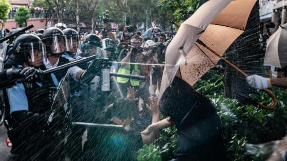 Police officers use pepper spray to disperse protesters after a rally in the Sheung Shui district on Saturday, July 13.