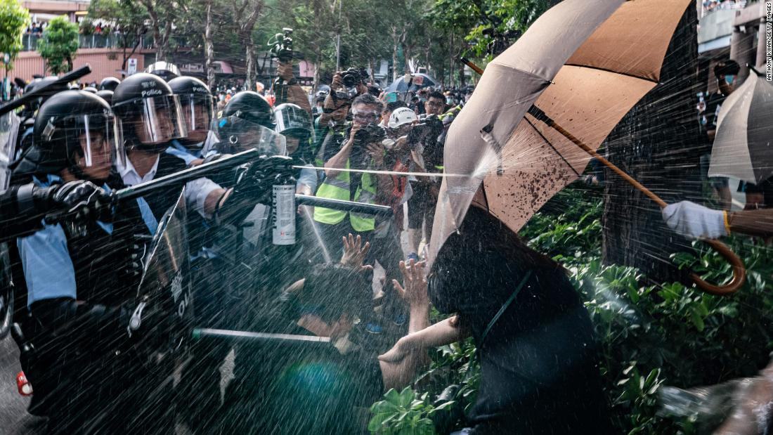 Police officers use pepper spray to disperse protesters after a rally in Sheung Shui district on July 13.