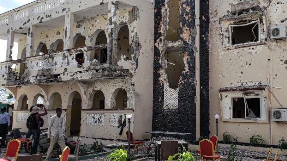 TOPSHOT - A man passes in front of the rubbles of the popular Medina hotel of Kismayo on July 13, 2019, a day after at least 26 people, including several foreigners, were killed and 56 injured in a suicide bomb and gun attack claimed by Al-Shabaab militants. - A suicide bomber rammed a vehicle loaded with explosives into the Medina hotel in the port town of Kismayo before several heavily armed gunmen forced their way inside, shooting as they went, authorities said. (Photo by STRINGER / AFP) (Photo credit should read STRINGER/AFP/Getty Images)