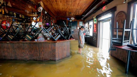 A man stands in floodwaters Saturday at Don'z On the Lake in Mandeville, Louisiana.