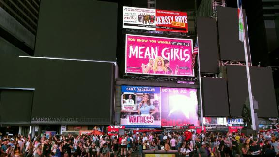 Times Square's billboards are black as people fill the street.